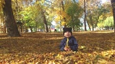 nevető : Little baby boy sitting on grass and fallen leaves in park on bright and sunny early autumn day looking at yellow leaf in hand and smiling. Happy baby boy throws autumn leaves and laughs outdoors.