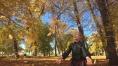 buttare : Adorable happy school girl throwing the fallen leaves up, playing in the autumn forest. Beautiful girl having fun in autumn park. Slow motion. Filmati Stock