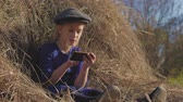 strohhut : Young cute girl with a cap having fun, sits in a haystack and use phone. Little girl sitting on hay. Stock Footage