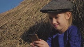 saman : Young cute girl with a cap having fun, sits in a haystack and use phone. Little girl sitting on hay. Stok Video