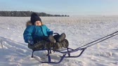 szánkó : Little boy enjoying a sleigh ride. Baby on the sleigh. Children play outdoors in snow. Cheerful winter vacation. Winter fun.