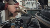 Car maintenance servicing mechanic pouring new oil lubricant into the car engine. Pouring fresh new clean synthetic oil into car engine. Change engine oil of your car. Stock mozgókép