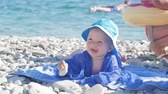 Cute little baby boy with a hat sitting on the beach and smiling.