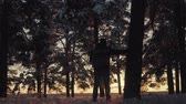 Hiker with backpack walking in the pine forest covered with fresh deep snow at sunset. Low angle view of tourist walking on the path with fresh deep snow. Winter activity and recreation concept. Stock Footage