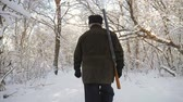 Hunter walking in the snowy winter forest. Winter hobby, sun, hunting concept. Filmati Stock