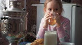 A little girl is drinking tea at the table.