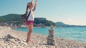 denge : Little girl builds a pebble tower sitting on the beach by the sea. The concept of a childs dream.
