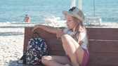 lody : Teenage girl on summer holidays, talking sitting on seaside bench with ice cream. Child eating ice cream on beach.
