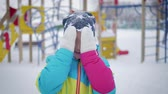 sbirciare : Little girl playing peek-a-boo with the camera at winter park. The concept of child joy and happiness. Filmati Stock