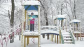 chlapec : Child playing in the Playground in the winter.