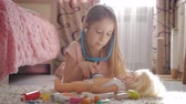 role : Beautiful little girl playing doctors with doll at home.