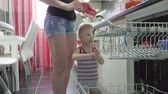 lave vaisselle : Baby boy helps mother to empty a dishwasher, casual lifestyle in real life interior.