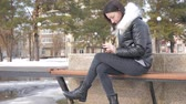 lavice : Cheerful woman on the phone in a city park sitting on a bench. Dostupné videozáznamy