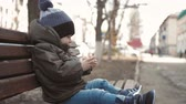 bağımlılık yapan : Little boy addictive smartphone sitting on bench in city street. Cute baby boy child with mobile phone on bench outdoor.