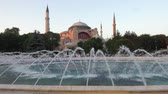 közel kelet : Video of fountain  in Sultan Ahmet Park with Hagia Sophia in the background at evening time, Istanbul, Turkey Stock mozgókép
