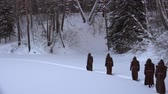 monastic : Group of monks in hood robe walking along winter snow trail in forest