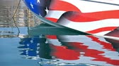 híbrido : Reflection of Yacht board with american flag in calm water