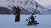 rood : Monks in brown cloaks of the order of St. Francis carries brushwood to the fire on mountains winter background