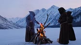 sect : Group of monks in brown cloaks of the order of St. Francis are warming themselves by the fire on the mountains