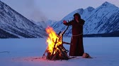 rood : Monk in brown cloaks of the order of St. Francis is warming hands by the fire on mountains winter background