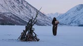 rood : Monks in brown cloaks of the order of St. Franciscarries wood to the fire on mountains winter background