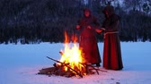 rood : Group of monks in brown cloaks of the order of St. Francis are warming themselves by the fire on the mountains