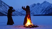 rood : Two monks in brown cloaks of the order of St. Francis are fighting near the fire on the mountains Stock Footage