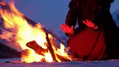 rood : Group of monks in brown cloaks of the order of St. Francis are warming hands on the fire on the mountains Stock Footage