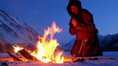 rood : Alone monk in brown cloaks of the order of St. Francis is warming hands by the fire and prays on mountains winter background Stock Footage