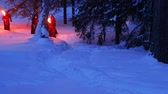 peregrino : Torchlight procession. Group of monks in hood robe walking along winter snow trail in forest