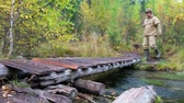해초 : Tourist man in boots and encephalitis suit crossing small wooden boardwalk bridge over forest creek in Altai mountains in rainy Autumn day 무비클립
