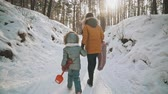 wintertime : Back view mother and daughter walk in winter park. Family fun in slow motion
