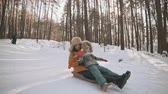 sanki : Young mother and little daughter having fun on sledge in winter park