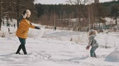 wintertime : Mother playing snow with little daughter in slow motion. Happy winter rest Stock Footage