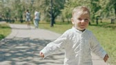 bliss : Little boy running from his parents. Happy family in slow motion