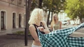 šortky : Smiling hipster womans running at city street. Cute girls have fun outdoors