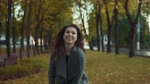 cores vibrantes : Cute girl in coat tossing leaves in autumn park and smiling in slow motion Stock Footage