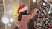 suéter : Pretty girl in sweater and santa cap decorates Christmas tree by red balls