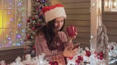 comunicare : Brunette girl in santa claus hat sending greeting sms using smart phone a porch Filmati Stock