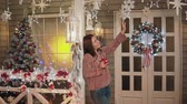 pullover : Pretty girl in sweater standing at porch with christmass tree at background Vidéos Libres De Droits