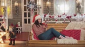 pullover : Pretty girl in christmas hat drinking tea sitting on christmass bench