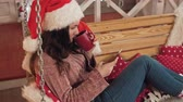 pullover : Pretty girl in christmas hat texting on phone. Woman greeting with Christmas Vidéos Libres De Droits