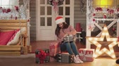 bright clothes : Girl in santa cap and sweater wrapping christmas gifts sitting at house porch