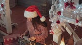 originales : Pretty girl in Santa hat wrapping gifts presents Archivo de Video