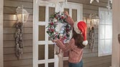 pullover : Pretty woman in santas hat hanging Christmas wreath on white door in house