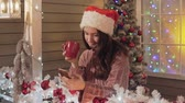 pullover : Brunette woman in santa hat texting message and greeting somebody with Christmas Vidéos Libres De Droits