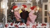 pullover : Happy family in pullovers hat hugging at Christmas porch. New year tree Vidéos Libres De Droits