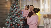 Young happy family decorating Christmas tree together at porch in slow motion Stock Footage