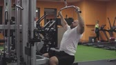Bodybuilder doing exercise on simulator in gym. Chest and back muscles