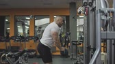 Man doing triceps exercises on block simulator in gym in slow motion Stock Footage